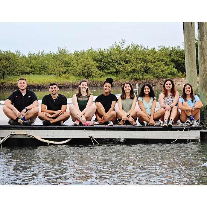 Group of students sitting on dock